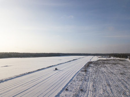Aerial view of a tractor removing snow from a takeoff runway