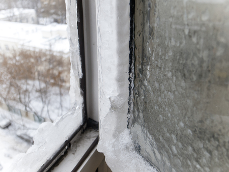 Open frosty window and a street covered with snow behind it
