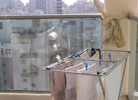 A balcony with washed laundry on the drying rack, a cityscape in the background 版權商用圖片