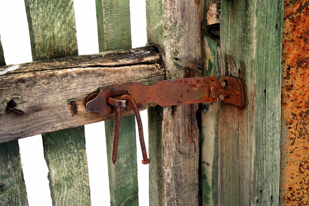 Closeup of a wooden gate locked with a nail