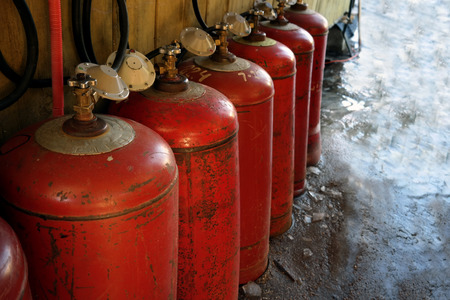 LPG bottles arranged in a row, outdoor close-up shot