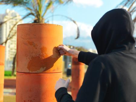 A man wearing hood punching a bag, outdoor cropped shot 版權商用圖片