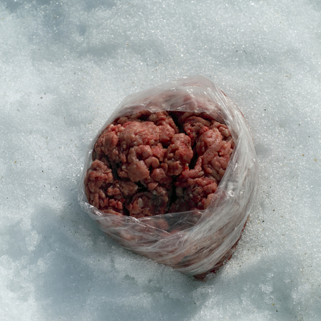 A plastic bag with minced meat placed on the snow, outdoor square shot