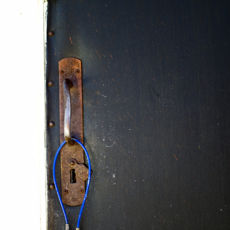 Old door with handle and hanging cable lock, outdoor square image