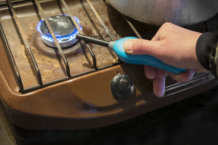 A hand starting a gas stove with a lighter, indoor closeup Stock Photo