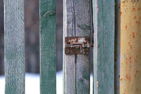A small rusty latch on a fence door, outside close-up