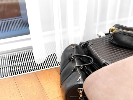 Luggage on the floor of hotel room next to the curtains and heating grill Stock Photo
