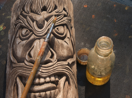 Covering wooden carved mask with protective lacquer, outdoor close-up Banco de Imagens