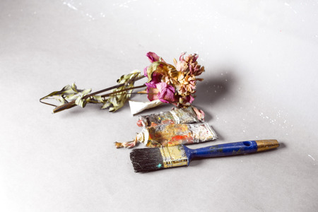 Artist equipment and withrered rose laid on a paper, studio still life Stock Photo