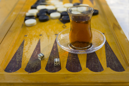 Playing backgammon and having traditional turkish tea, outdoor close-up Stock Photo