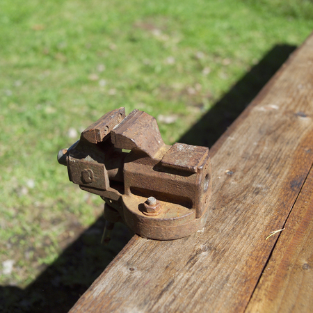 Old rusty vise mounted on a wooden bench, outdoor closeup