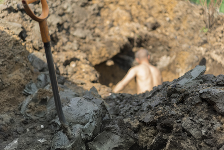 Shovel in the foreground and a worker, digging a hole in the blurred background