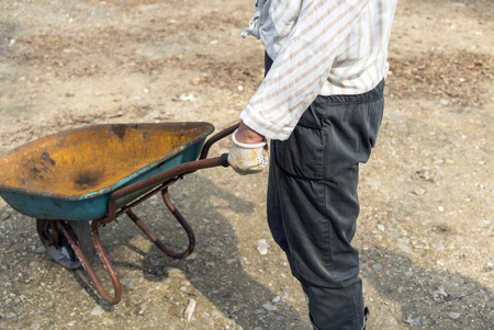 Female worker pushing a rusty old trolley, outdoor cropped shot 스톡 콘텐츠