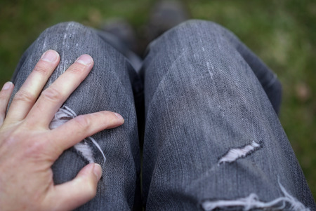 A man sitting in torn jeans and keeping hand on his knees, outdoor close-up
