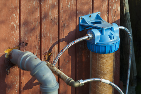 Water filter, hose and pipe mounted on a wooden house wall Reklamní fotografie
