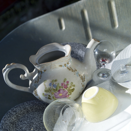 Stack of crockery in a metal tray, outdoor close-up