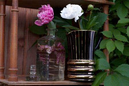 Beautiful pink and white peonies in vases placed on the wooden bookcase, outdoor close-up