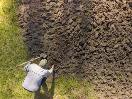 Aerial view of a man with shovel removing weeds from the ground