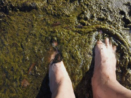 Overhead shot of the human bare feet standing in dirty water