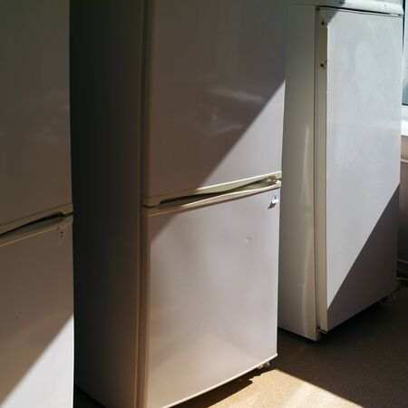 Three old fridges arranged in a row, indoor square shot