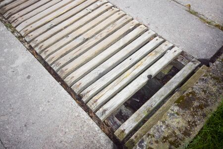 A gap in asphalt repaired with wooden planks, outdoor close-up Stok Fotoğraf