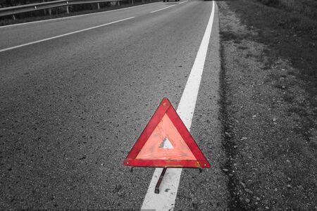 Triangle warning road sign on asphalt, selective color shot