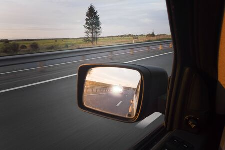 A car in a mirror with headlight high beam blinking, cropped shot Stock fotó
