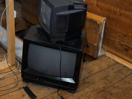 Stack of old TV sets seemingly not working, about to be thrown away, indoor shot