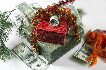 American dollars and  colorful gift boxes wrapped with tinsel, studio close-up
