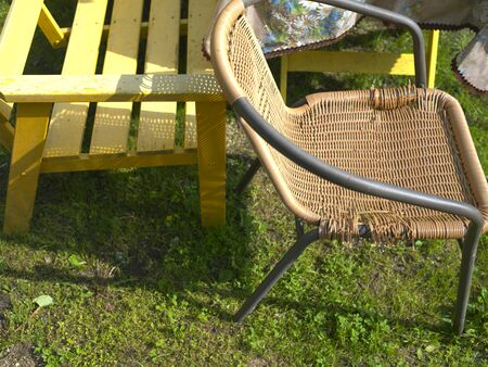 Closeup of a bench and wicker chair, outdoor summertime cropped shot