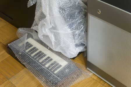 Synthesizer keyboard covered with foil and placed on a floor, indoor shot Foto de archivo