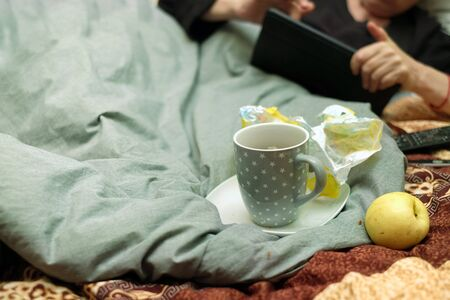 Candy wrappers cup and apple in a messy bed, a silhouette of a woman with tablet in hands in the blurred vackground