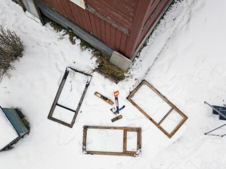 Old windows and work tools abandoned on the snow, aerial view