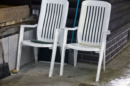 Two folding plastic chairs in a backyard, outdoor shot