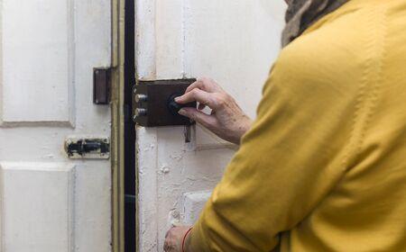 Female hands locking or unlocking entrance door, indoor cropped shot