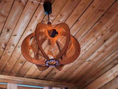 Decorative old fashioned lampshade mounted on wooden ceiling