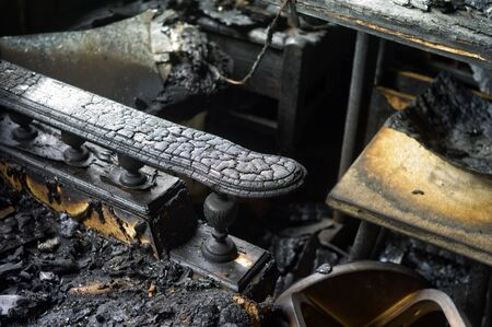 Burnt wooden armchair in a room destroyed by fire, indoor closeup