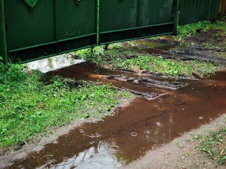 Mud and puddle in front of the metal gate, outdoor shot