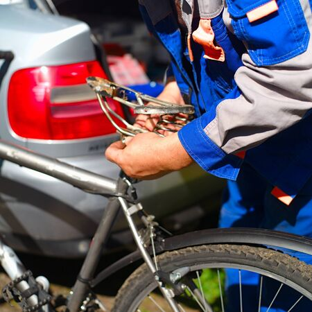 Hands of mechanic replacing a bicycle seat, an open car boot in the background Stock Photo
