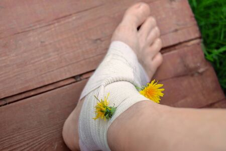 Injured bare foot in bandage decorated with plants for fun