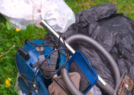 Discarded damaged vacuum cleaner left with garbage, outdoor closeup Stock Photo - 154543513