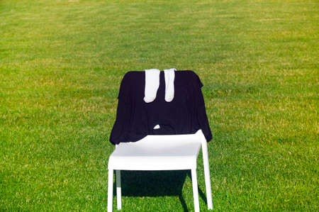 Socks and t-shirt drying on a chair, placed on the lawn
