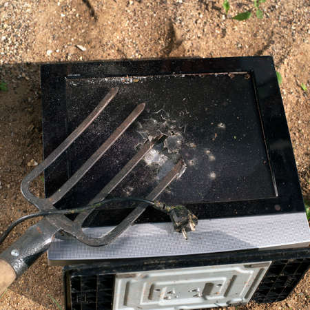 Old computer screen damaged with  pitchfork  and abandoned on the sand Stock Photo