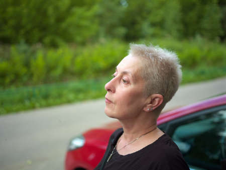 SZtreet portrait of female driver posing bext to her car