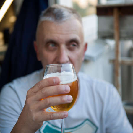 A man posing with a lager in his hand, focus in the foreground Stock Photo