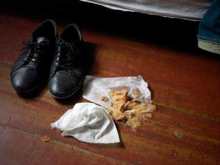 Messy floor with vomit next to a bed, indoor closeup Stock Photo