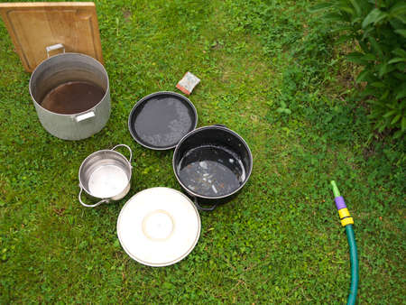 Washing casseroles placed on the grass next to a garden hose
