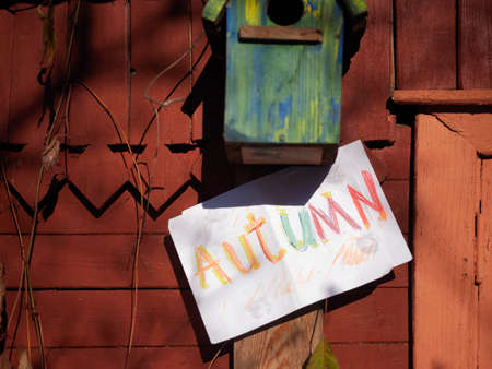 A word Autumn written on a paper and empty birdhouse on the wall, concept of season shift