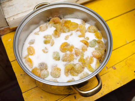 A stainless steel casserole with yellow fruits in sugar, indoor closeup Stock Photo