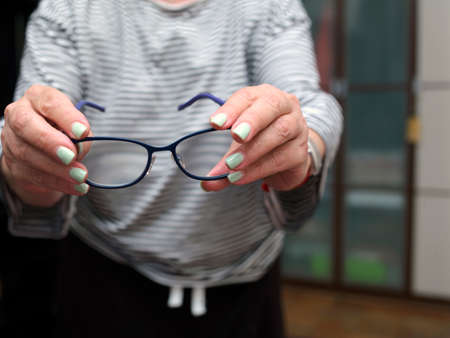 the spectacles in female hands with manicured nails, indoor closeup